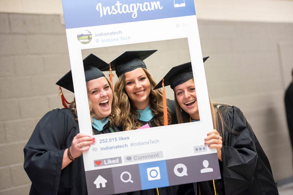 Three students smiling while holding an instagram sign frame