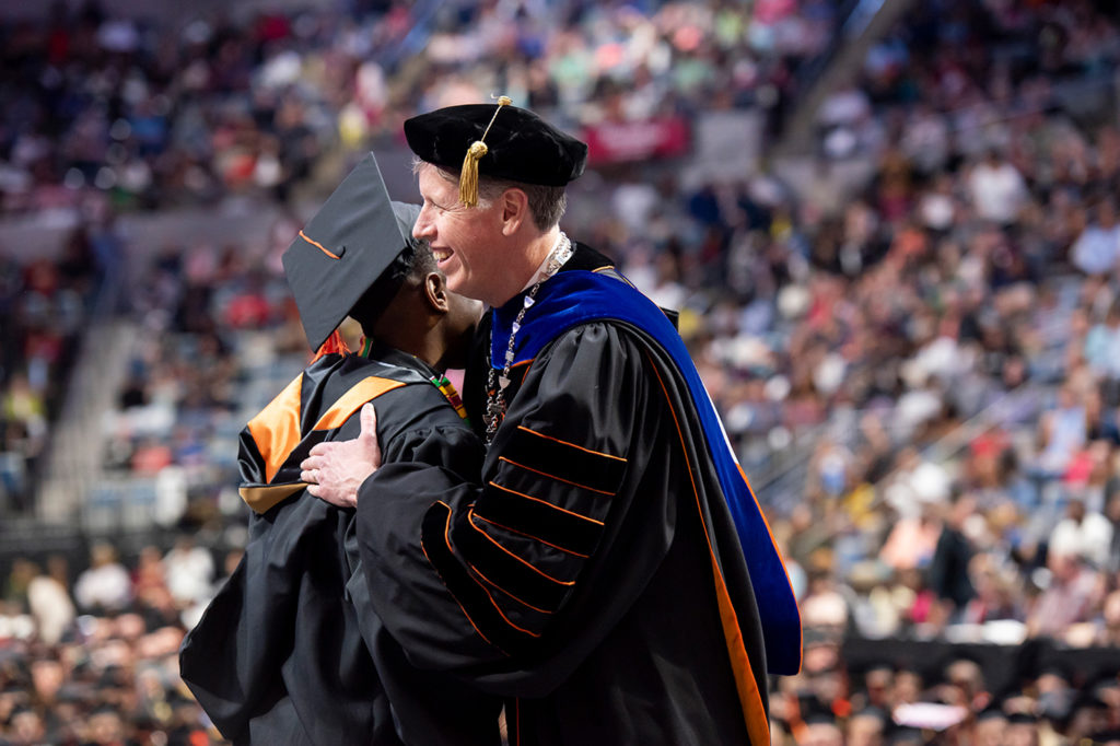 President Dr. Karl Einolf congratulating a master's graduate recipient on stage during the 2018 Commencement Ceremony