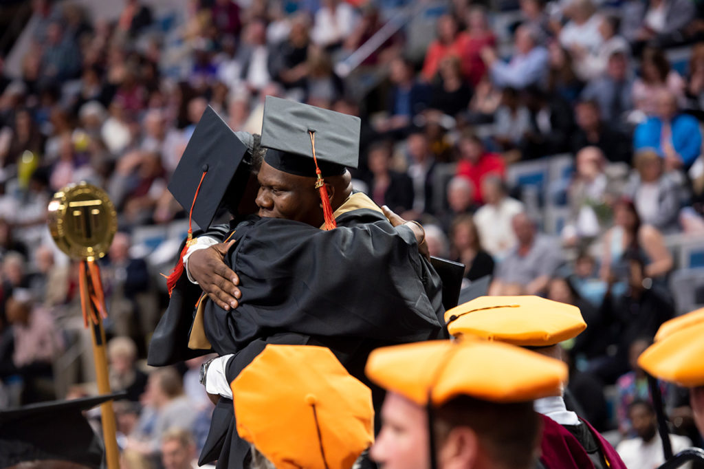 Darius Darling hugging a graduate during the 2018 Commencement Ceremony