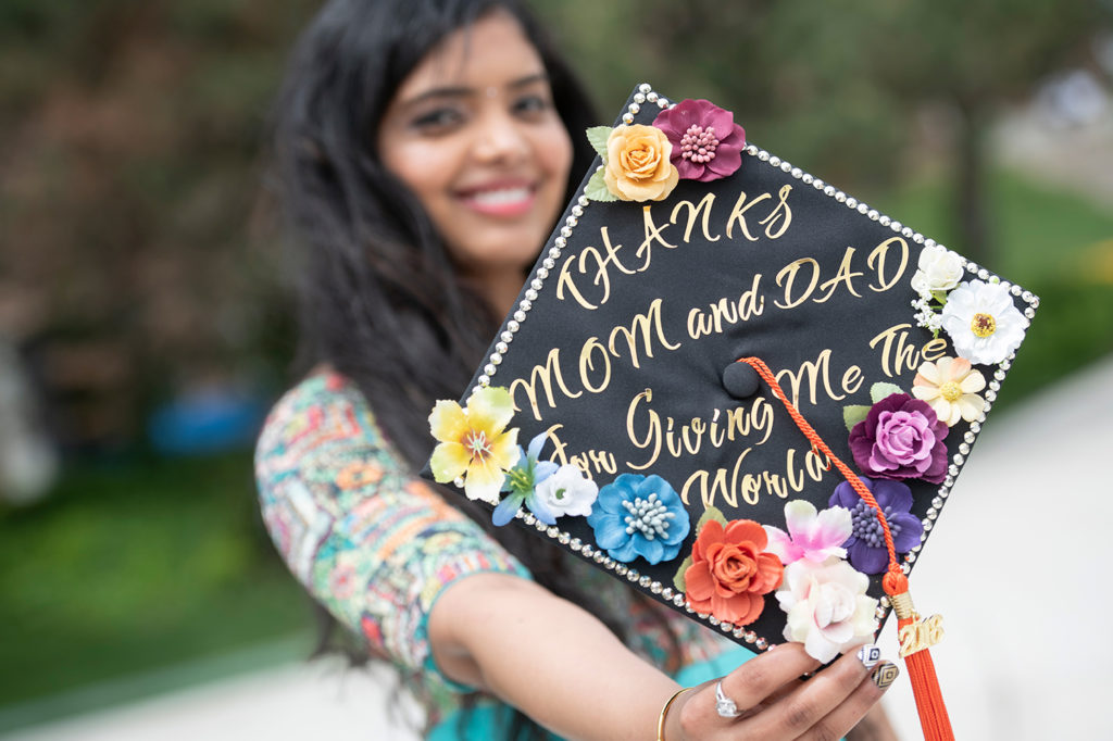 A young woman holding her graduate cap that says thanks mom and dad for giving me the world.