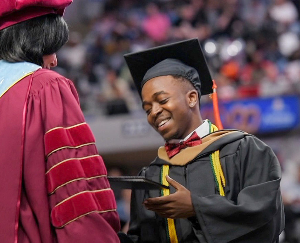 A student receiving his diploma on stage during graduation