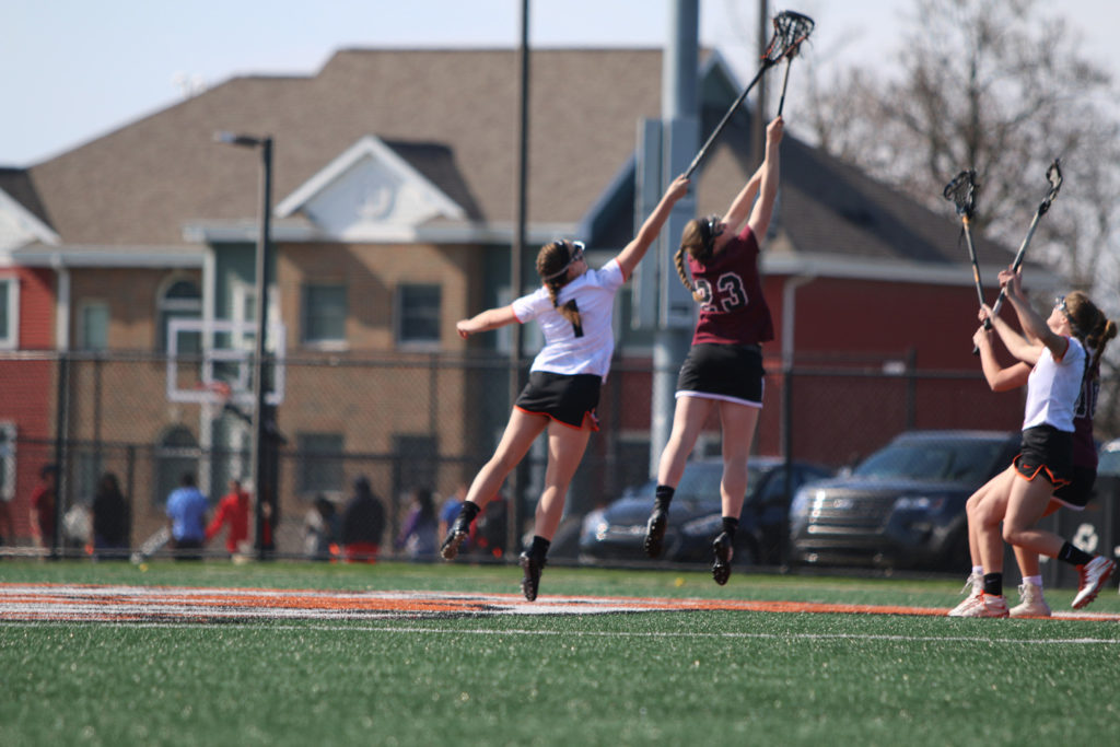 Lacrosse players jumping to catch the ball