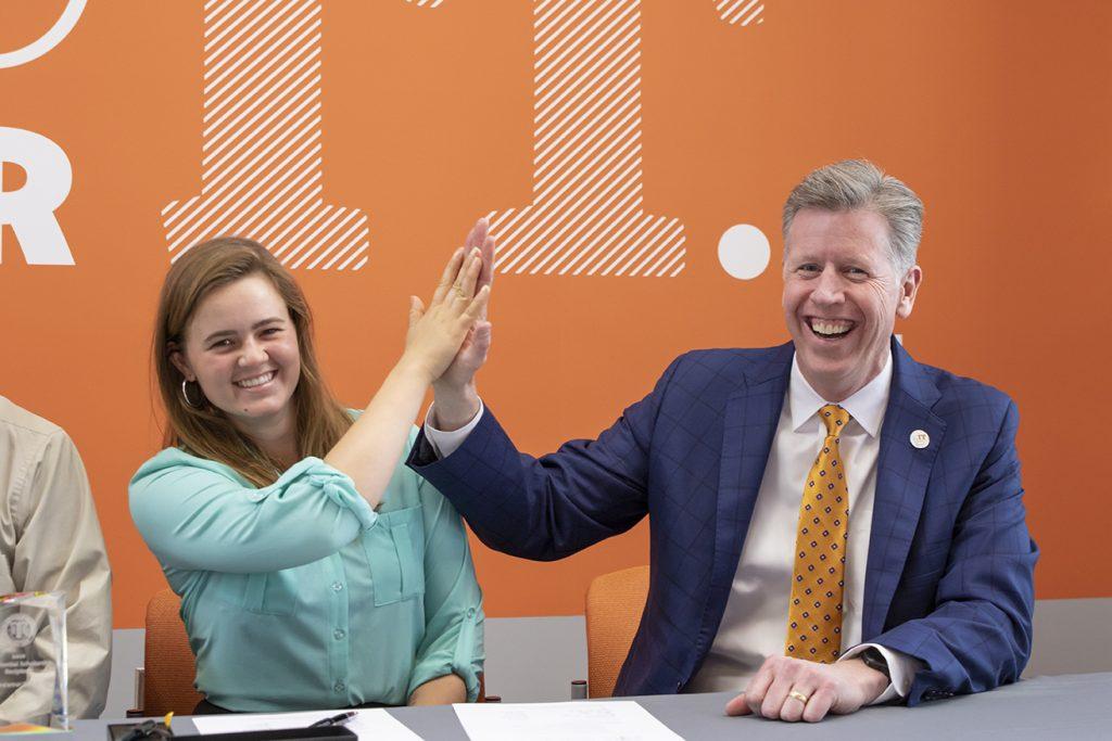 Dr. Einolf hi-fives a Presidential Scholarship winner, 2019.