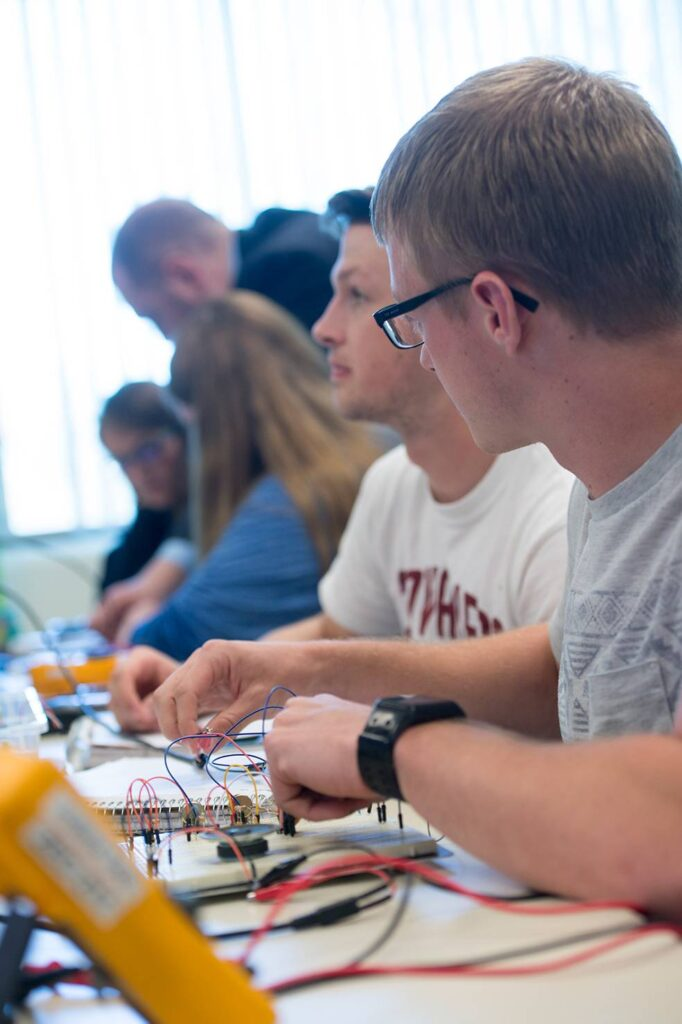 Dr. David Rumsey assisting students in his Electrical Engineering class